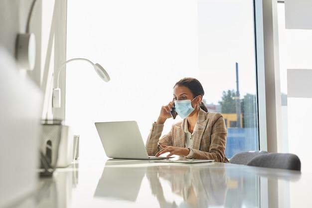 Ritratto di donna d'affari di razza mista che indossa la maschera e parla da smartphone mentre si lavora in ufficio bianco, copia dello spazio
