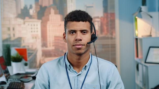 Ritratto dell'operatore del servizio clienti di razza mista in un auricolare sorridendo alla telecamera