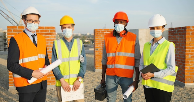 Ritratto di squadra di costruttori di uomini e donne di razza mista in caschi e maschere mediche in piedi in cima alla costruzione con bozze di piani di costruzione. coronavirus. ingegneri e architetti in costruzione.