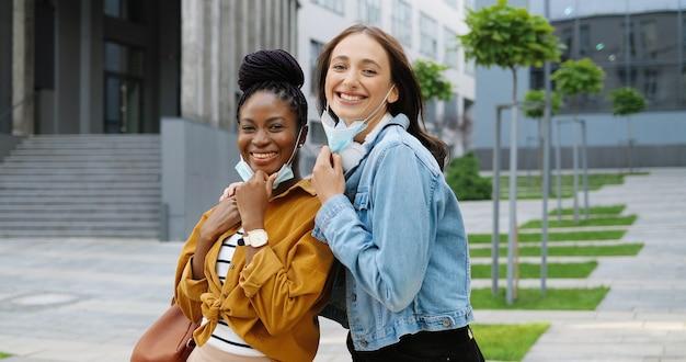 Ritratto di razze miste giovani femmine allegre migliori amici togliendosi maschere mediche in strada e sorridente. studenti di ragazze felici multietniche all'aperto. donne afroamericane e caucasiche. pandemia.