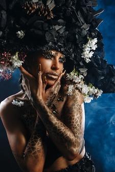 Ritratto di una modella con un copricapo e un vestito di carbone. c'è fumo blu dietro il modello