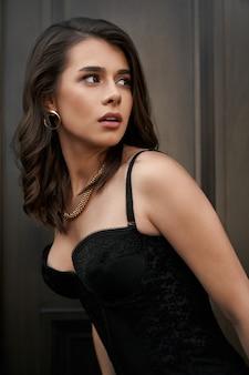 Ritratto di modello indossando corsetto in posa vicino alla porta di legno.