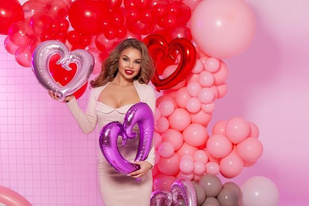 Ritratto di modello con trucco naturale. palloncini rossi e rosa sul muro.
