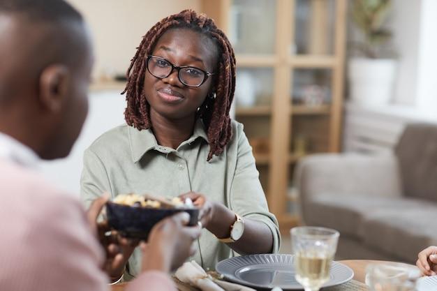Ritratto di una moderna coppia afro-americana che si gode la cena insieme a casa, si concentra sulla giovane donna sorridente che condivide il pasto con il marito, copia spazio