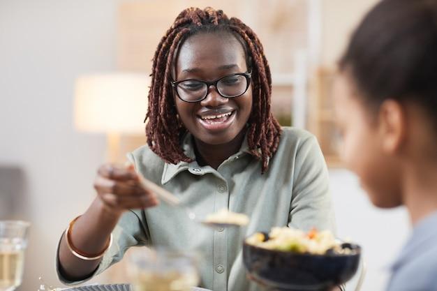 Ritratto di una moderna famiglia afro-americana che si gode la cena insieme a casa, si concentra sulla giovane donna sorridente che condivide il pasto fatto in casa con la figlia