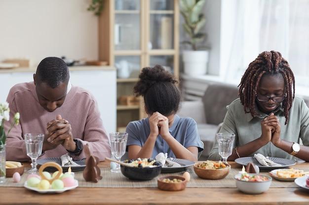 Ritratto di una moderna famiglia afro-americana che dice grazia a tavola mentre celebra la pasqua a casa, copia spazio