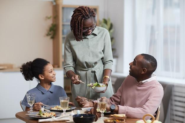 Ritratto di una moderna donna afro-americana che serve cibo per la famiglia mentre si gode la cena insieme in un accogliente interno di casa, copia spazio