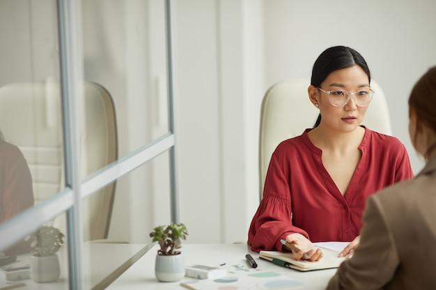 Ritratto della donna di affari asiatica moderna che parla al cliente mentre lavora alla scrivania nel cubicolo bianco dell'ufficio, spazio della copia
