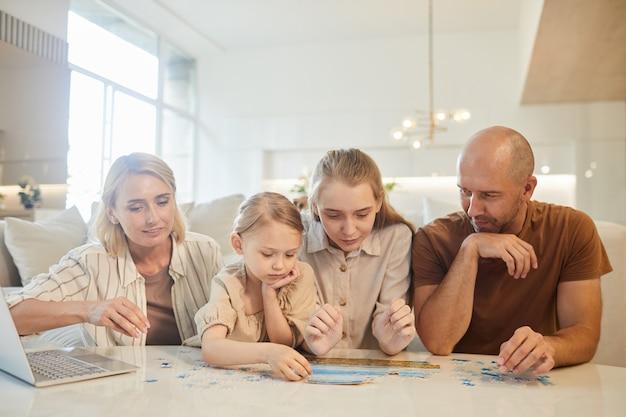 Ritratto di famiglia moderna con due bambini che risolvono puzzle insieme mentre vi godete il tempo al chiuso a casa
