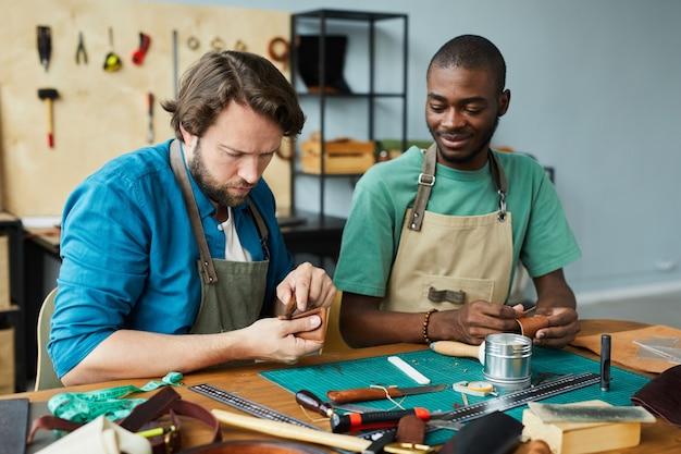 Ritratto di un moderno artigiano maschio che insegna a un giovane apprendista nello spazio della copia dell'officina dei pellettieri