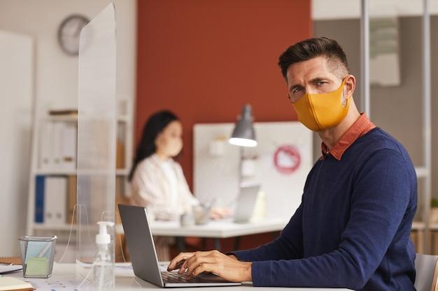 Ritratto di uomo maturo moderno che indossa la maschera e guardando la fotocamera mentre si utilizza il computer portatile alla scrivania in ufficio, copia dello spazio