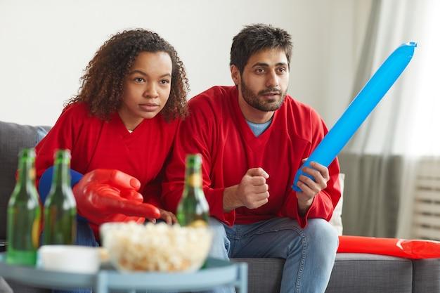 Ritratto di coppia moderna di razza mista che guarda lo sport in tv a casa e fa il tifo per una partita intensa mentre indossa le uniformi della squadra rossa