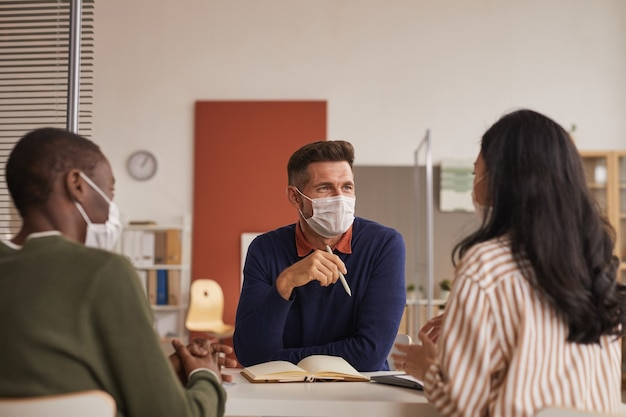 Ritratto del team multietnico moderno che indossa maschere durante la riunione di lavoro in ufficio, copia dello spazio