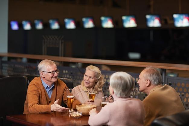 Ritratto di una moderna coppia anziana che beve birra al bar e chiacchiera mentre si gode la serata fuori con gli amici al bowling, copia spazio