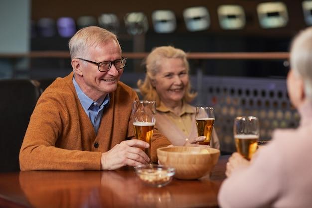 Ritratto di una moderna coppia anziana che beve birra al bar e ride mentre si gode la serata fuori con gli amici, copia spazio