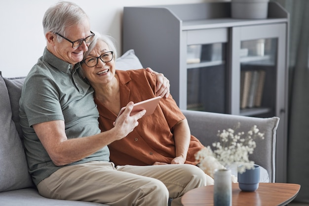 Ritratto di una moderna coppia anziana che utilizza tablet a casa e sorride felicemente mentre è seduta sul divano in interni minimi, copia spazio