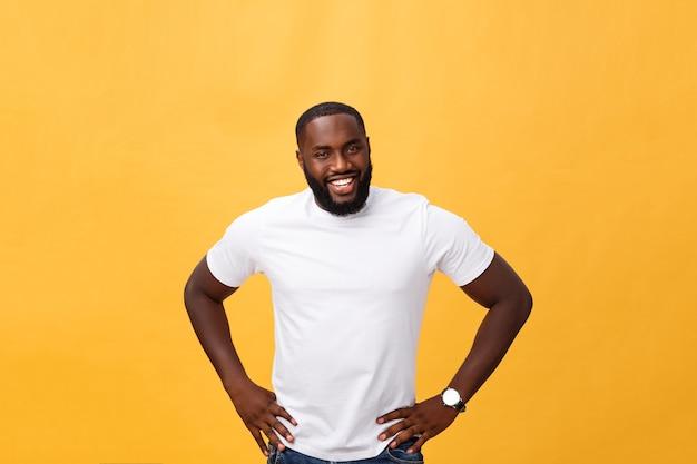 Ritratto di un moderno giovane uomo nero sorridente in piedi su sfondo giallo isolato.