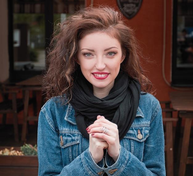 Ritratto di una giovane donna moderna sullo sfondo di un caffè di strada