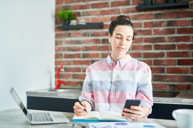 Ritratto della giovane donna moderna che per mezzo dello smartphone mentre lavorando a casa o facendo i compiti, spazio della copia