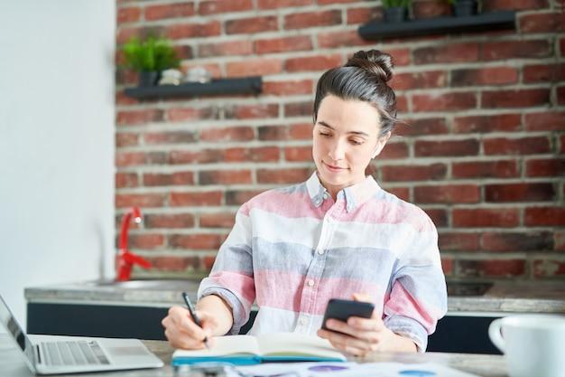 Ritratto di giovane donna moderna che lavora a casa o facendo i compiti, copia spazio