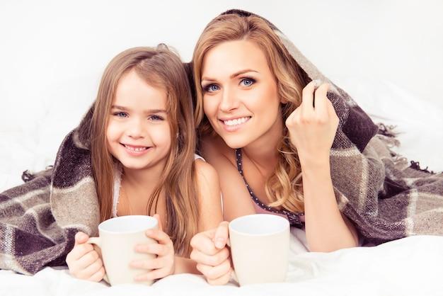 Ritratto di mamma e figlia che si crogiolano sotto il plaid con tazze di latte caldo