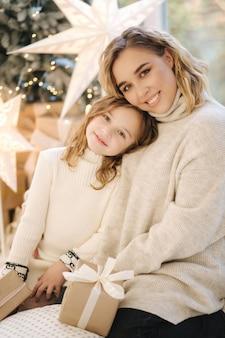 Ritratto di mamma e figlia nel periodo natalizio. la famiglia felice ha trascorso del tempo insieme durante le vacanze