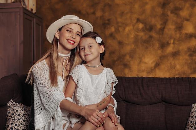 Ritratto mamma e figlia in abiti bianchi all'interno del soggiorno. famiglia di bellezza sul divano di casa. concetto di educazione dei genitori, valori familiari e amore per i bambini. copia spazio per il sito
