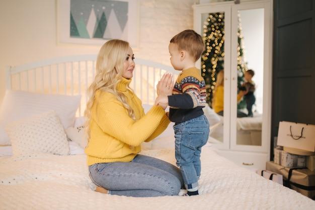 Ritratto di mamma e figlio seduti su un letto a casa vicino all'albero di natale, tutti sorridono. natale in famiglia. felicità.