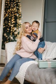 Ritratto di mamma e figlio seduti su un pullman a casa vicino all'albero di natale, tutti sorridono. natale in famiglia. felicità.