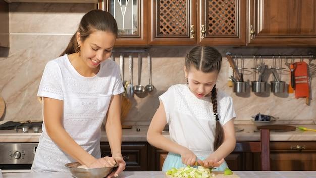 Ritratto di madre e figlia stanno cucinando insieme torta di mele in cucina, la mamma sta impastando un impasto e sua figlia adolescente sta tagliando la mela.