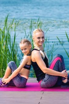 Ritratto di madre e figlia seduti sul tappetino da yoga