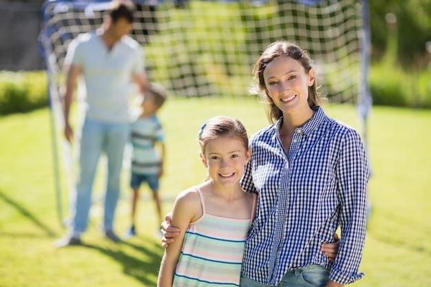 Ritratto di madre e figlia in piedi nel parco