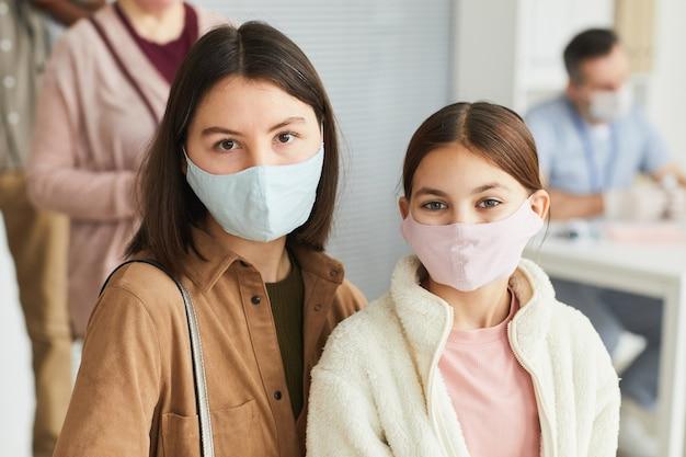 Ritratto di madre e figlia che indossano maschere e guardano la telecamera mentre aspettano in fila al centro medico