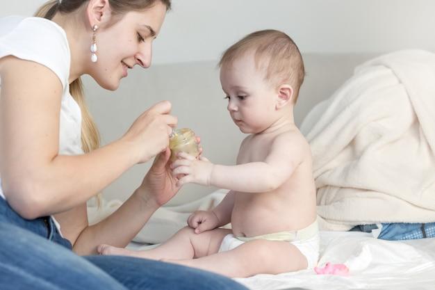 Ritratto di madre che allatta il suo adorabile bambino sul letto con salsa di frutta da un barattolo di vetro