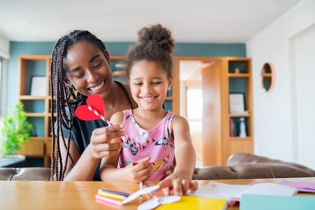Ritratto di una madre e sua figlia che sorridono e trascorrono del tempo insieme mentre si rimane a casa. concetto monoparentale. nuovo concetto di stile di vita normale.