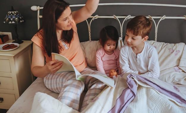 Ritratto di madre che legge un libro di storie ai suoi figli figlia e figlio seduti nel letto. concetto di tempo libero per la famiglia nel fine settimana.