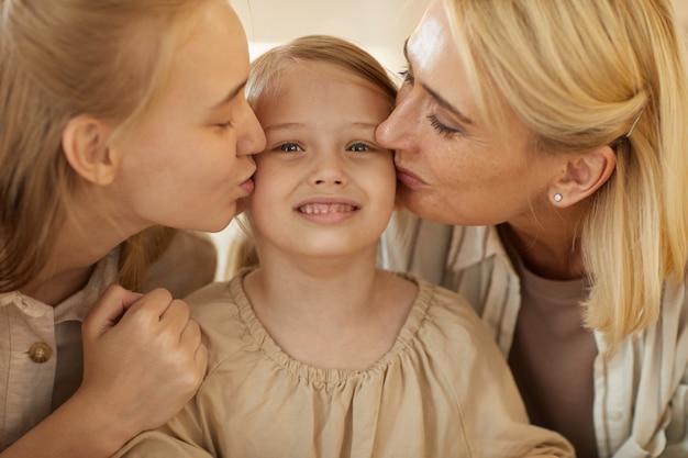 Ritratto di madre e sorella che baciano bambina sveglia su entrambe le guance, legami familiari e concetto di generazioni