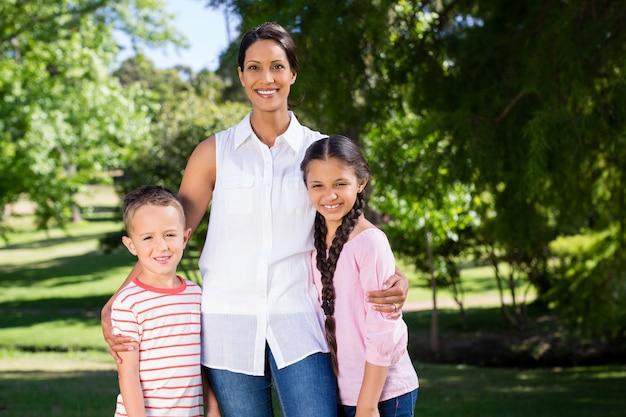 Ritratto della madre che sta con i suoi bambini in parco