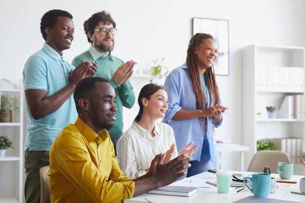 Ritratto del team multietnico di affari che applaude e sorride mentre ascolta la presentazione o celebra il successo in ufficio