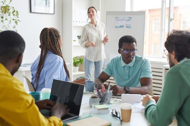 Ritratto del team multietnico di affari che discute del progetto mentre era seduto al tavolo nella sala conferenze con manager in piedi dalla lavagna