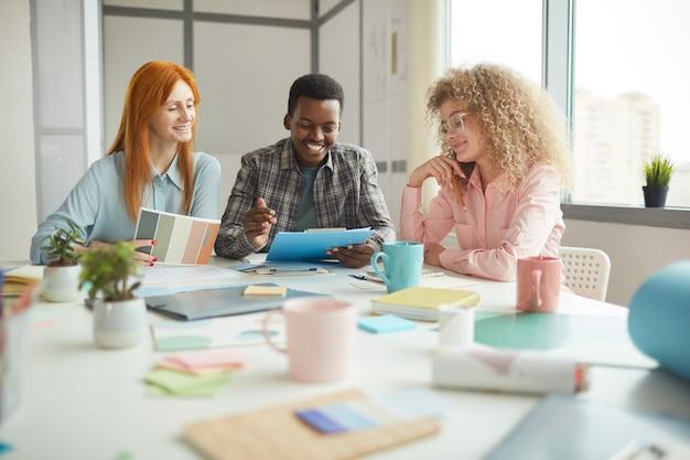 Ritratto del team di designer multietnici sorridente allegramente mentre discute il progetto creativo in un ufficio moderno, copia dello spazio