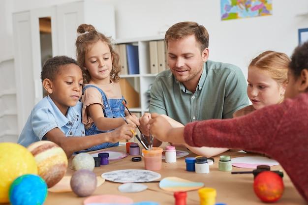Ritratto di un gruppo multietnico di bambini che tengono i pennelli e dipingono il modello del pianeta mentre si godono le lezioni di arte e artigianato a scuola o nel centro di sviluppo
