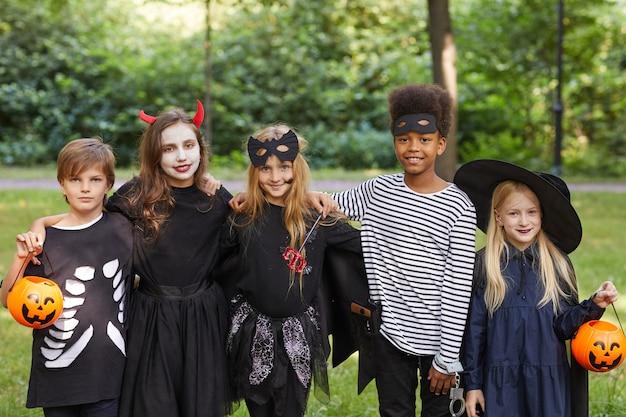 Ritratto di un gruppo multietnico di bambini che indossano costumi di halloween stando in piedi all'aperto e