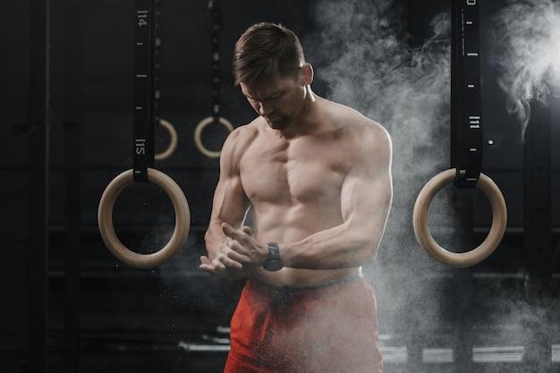 Ritratto di atleta crossfit muscolare che applaude le mani e si prepara per l'allenamento in palestra