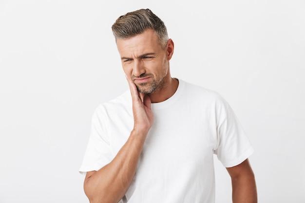Ritratto di un uomo muscoloso di 30 anni con setola che indossa una maglietta casual che si tocca la guancia e soffre di mal di denti isolato su bianco