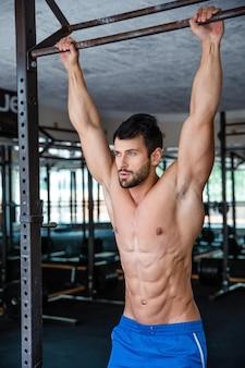 Ritratto di un uomo muscoloso che si stringe sulla barra orizzontale in palestra