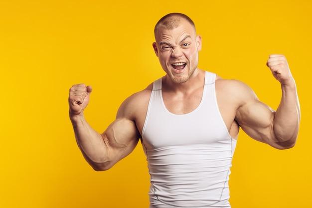 Ritratto di uomo muscoloso in camicia bianca che mostra bicipiti, in piedi sopra la parete gialla isolata