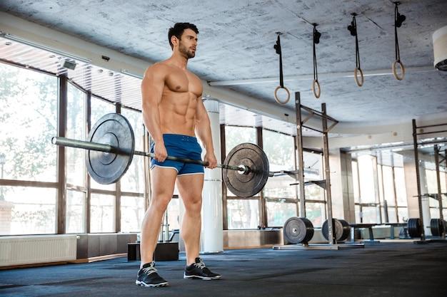 Ritratto di un uomo muscoloso che si allena con bilanciere in palestra