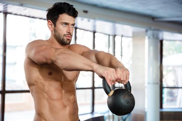 Ritratto di un uomo muscoloso che si allena con la palla bollitore in palestra