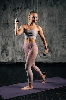 Ritratto di giovane donna atletica muscolare con un bel corpo perfetto che indossa abbigliamento sportivo facendo esercizio con sollevamento pesi e affondo in avanti. femmina caucasica di forma fisica che posa nello studio.